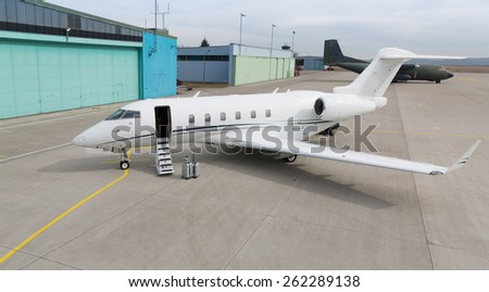 corporate private jet with luggage in front - stock photo