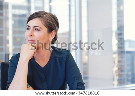 Corporate professional business woman in city office with buildings blurred through window in background - stock photo