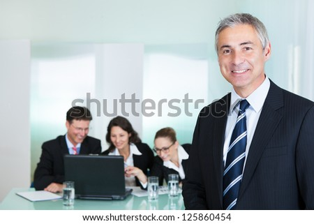 Corporate promotion and leadership concept with a successful handsome smiling businessman standing in the foreground while his colleagues