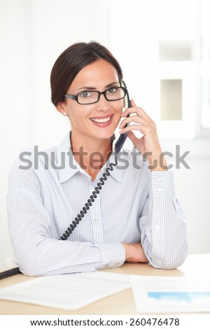 Corporate secretary with glasses happily talking on the phone while smiling in her office - stock photo