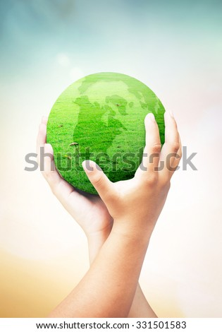 Corporate social responsibility (CSR) concept: global of grass in two human hands on blurred nature background.