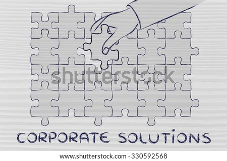 corporate solutions, hand about to add the missing piece to a jigsaw puzzle