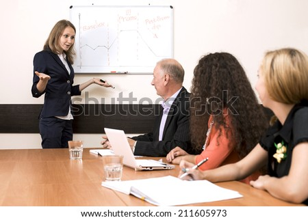 Corporate training. The female trainer is presenting the subject standing near wall chart while participants are listening