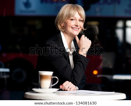 Corporate woman enjoying break from work in cafe near her office. - stock photo