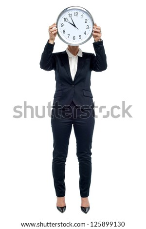 Corporate woman holding up clock in front of her face. Time is precious, make use of it. - stock photo