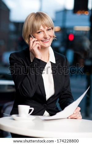 Corporate women verifying reports while communicating on phone - stock photo