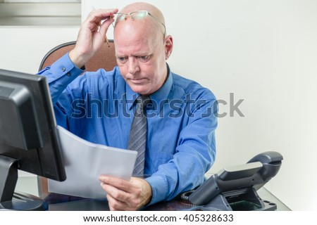 Corporate worker at desk comparing written notes with computer data