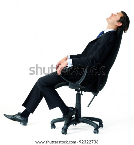 Corporate worker in business suit leans back on his office chair, daydreaming about his upcoming vacation - stock photo