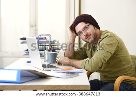 corporate young attractive hipster businessman working at home office as freelancer in casual beanie leaning on computer desk smiling happy and confident  in creative freestyle business
