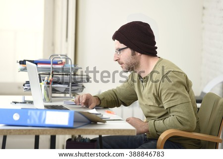 corporate young attractive hipster businessman working with computer laptop at home office as freelancer in casual beanie desk smiling happy and confident  in creative freestyle business