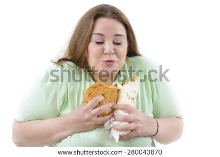 Corpulent woman having addiction to unhealthy food. Happy holding some high calories food. - stock photo