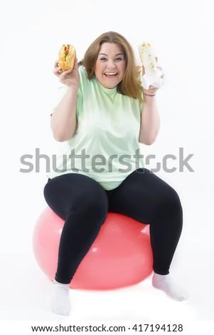 Corpulent woman having addiction to unhealthy food sitting on fitness ball - stock photo
