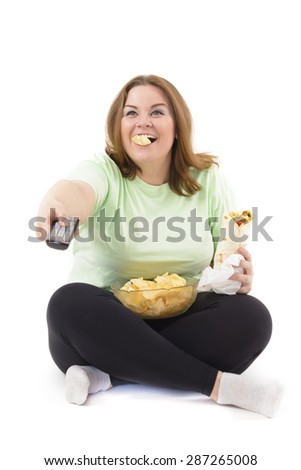 Corpulent woman with addiction to unhealthy food. Holding a remote controller - stock photo