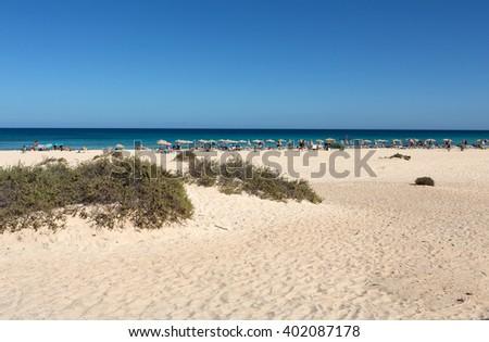 CORRALEJO, FUERTEVENTURA, SPAIN - SPETEMBER 17, 2015: Tourists rest on Corralejo Beach on Fuerteventura, Canary Islands - stock photo