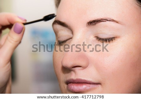 Correction of eyebrow tweezers, eyebrow henna painting, beautiful young girl beauty salon, plucking and simulation form a perfect eyebrows, tattoos and permanent make-up