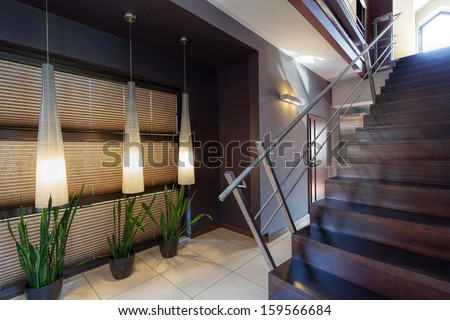 Corridor, green plants and staircase with metal banister - stock photo