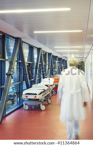 corridor in hospital with two beds and the door closed to the ambulance with doctor blurred - stock photo