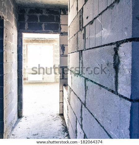 Corridor of grey large brick walls - stock photo