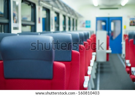 Corridor with rows of seats with headrests in modern suburb commuter train