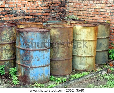 Corroding oil drums in a deserted building pollute the ground  - stock photo