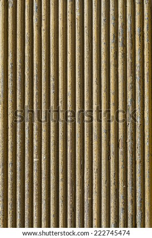 Corrugated metal sheet covered with old yellow paint - stock photo