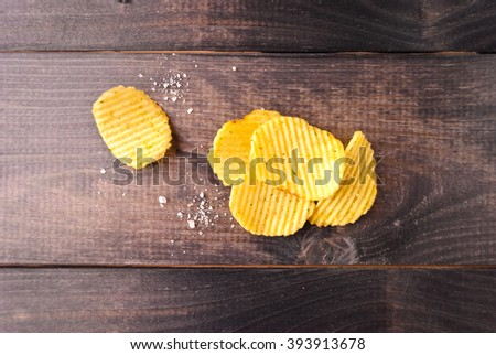 Corrugated potato chips and salt on brown wooden background - stock photo