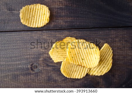 Corrugated potato chips and salt on rustic wooden background - stock photo