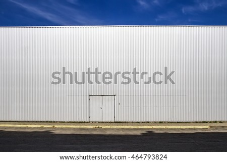Corrugated sheet metal wall with a door, the street shadows and blue sky. Outdoor. Industrial look. Digital background for photographers.
