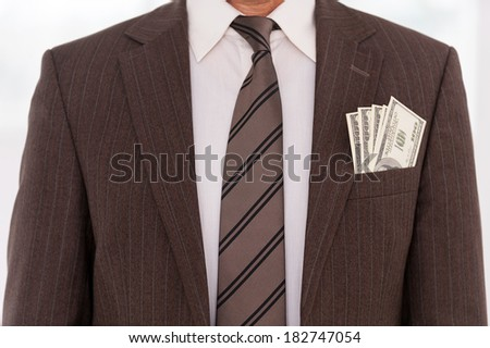 Corrupted businessman. Close-up of businessman in formalwear with money stretching out of his pocket