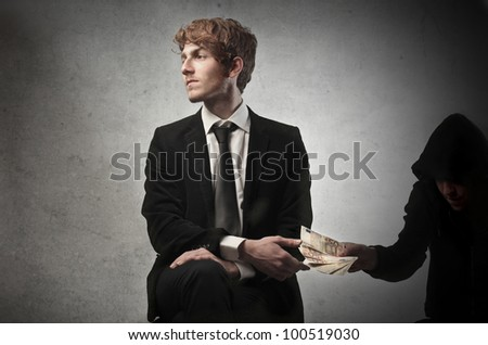 Corrupted young businessman accepting some money from a crook - stock photo