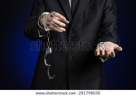 Corruption and bribery theme: businessman in a black suit with handcuffs on his hands on a dark blue background in studio isolated - stock photo