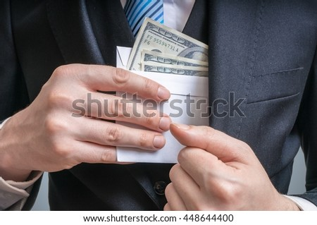 Corruption concept. Businessman is hiding letter full of money or bribe in suit jacket.