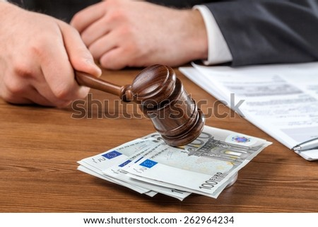 Corruption. Male Judge Striking The Gavel Euro Note In A Courtroom - stock photo
