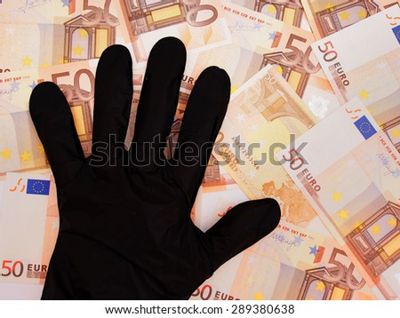 Corruption, misuse of EU funds. Black gloved hand stealing Euros. Note - only part notes shows to comply with copyright. - stock photo