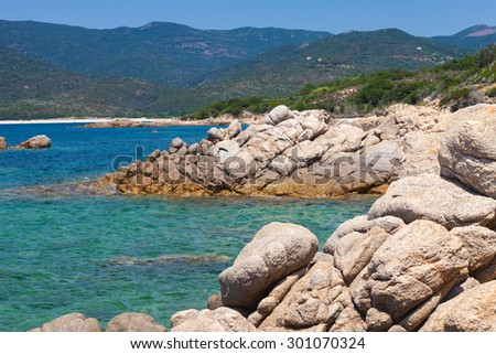 Corsica island, wild coastal landscape with stones in blue sea water. Selective focus on a foreground - stock photo