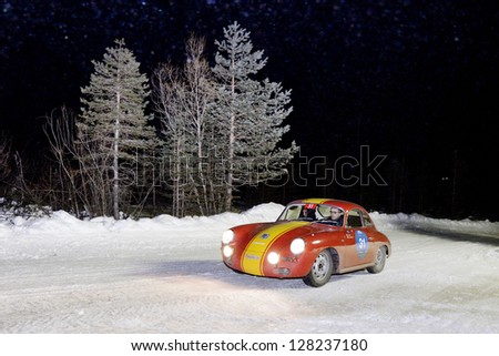 CORTINA D'AMPEZZO (BL) ITALY - JANUARY 26: A red/yellow Porsche 356 coupe 4 built in 1964 takes part to the Winter Marathon on January 26, 2013 in Cortina d'Ampezzo (BL) - stock photo