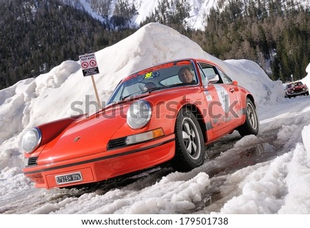 CORTINA D'AMPEZZO, ITALY - FEBRUARY 21: A red Porsche 911 S takes part to the WinteRace classic car race on February 21, 2014 in Cortina d'Ampezzo. This car was built in 1973. - stock photo
