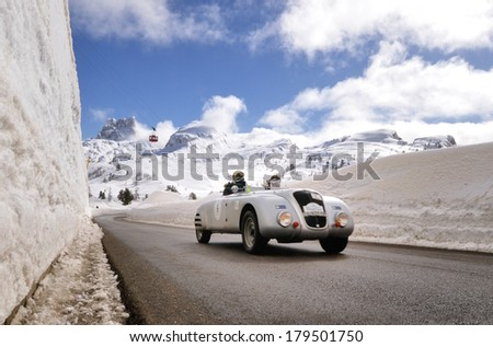 CORTINA D'AMPEZZO, ITALY - FEBRUARY 21: A silver Lancia Aprilia Barchetta takes part to the WinteRace classic car race on February 21, 2014 in Cortina d'Ampezzo. This car was built in 1938. - stock photo