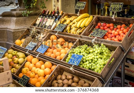 CORTONA, ITALY - JUNE 26, 2015: assortment of toscan ripe fruits and wine bottles in historic Cortona town in Italy