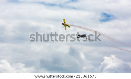 Coruna, Spain - July 17, 2014: Two planes model Yak-52 performing aerobatics, one crossed in front of the other.