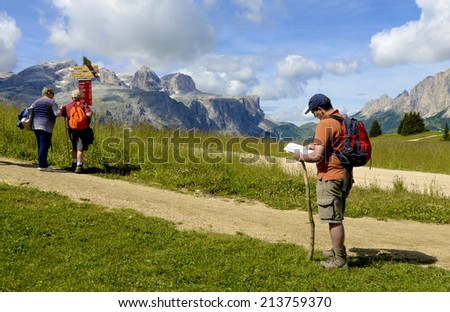 CORVARA ITALY-AUGUST 08, 2014: a man checks his map and a couple check footpath signs, surrounded by the rocky Dolomites mountains, in Corvara.
