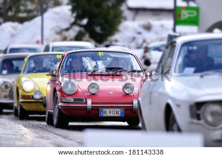 CORVARA, ITALY - FEBRUARY 21: A red Porche 912, a yellow Porsche 911 and other cars take part to the WinteRace classic car race on February 21, 2014 in Corvara. Focus on the red Porsche - stock photo