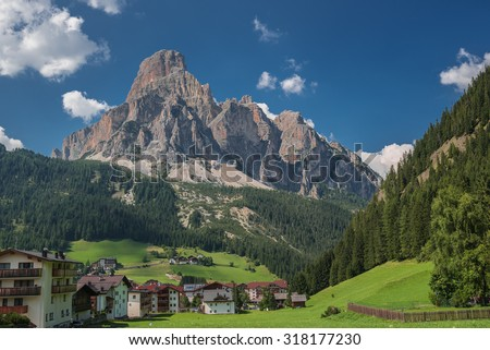 CORVARA village with MOUNT SASSONGHER (2,665 m), VAL BADIA, ITALY-August 10, 2015: A scenic view of the mountain peak above as seen from the village below, Dolomites, Trentino, Alto-Adige, South Tyrol