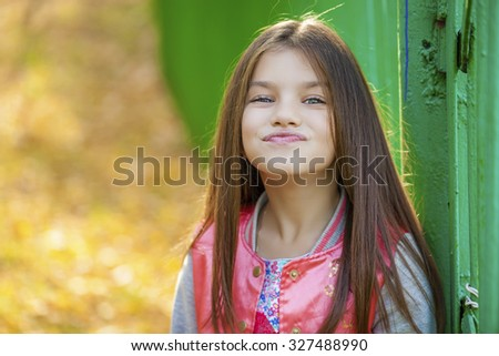 Cose up, Beautiful little girl on green background of summer city park