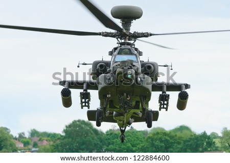 COSFORD, SHROPSHIRE, ENGLAND - JUNE 17: Boeing AH-64 Apache attack helicopter taking off at RAF Cosford on June 17, 2012 in Cosford, Shropshire, England. - stock photo