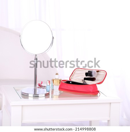 Cosmetic bag and mirror on table on light background - stock photo