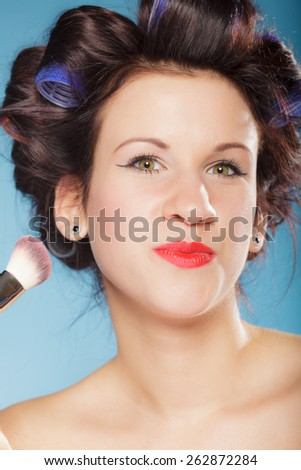 Cosmetic beauty procedures and makeover concept. Woman in hair curlers applying makeup blusher with brush. Girl gets blush on cheekbones, on blue - stock photo