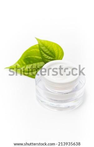 Cosmetic bottle container with green leaves, isolated on white background.