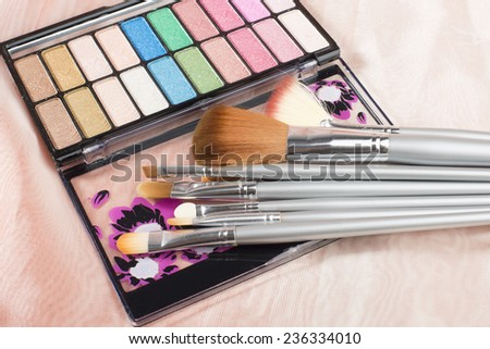Cosmetic  brushes and eyeshadow on the pink background - stock photo