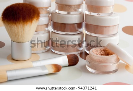 cosmetic brushes, make-up powder, blush, foundation, eyeshadow in plastic jars - stock photo